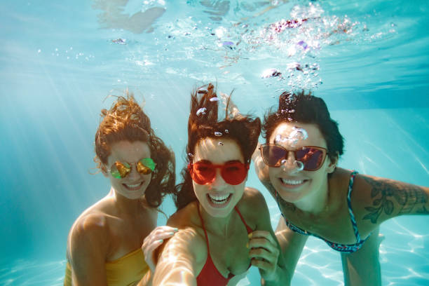 vrolijke vrienden maken selfie onderwater in zwembad - onder water stockfoto's en -beelden