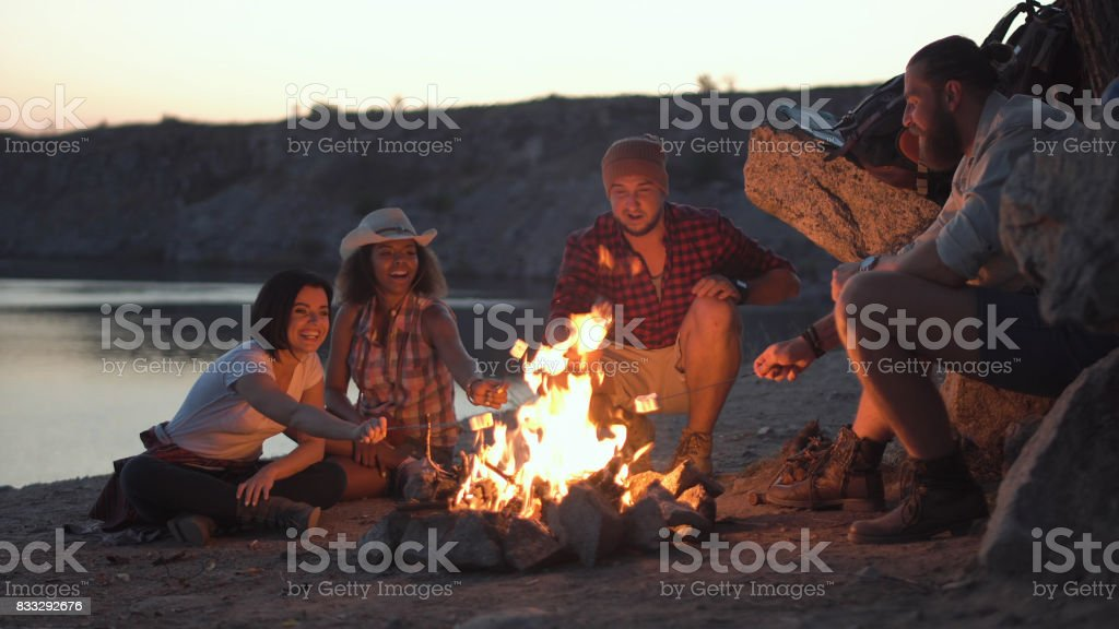 Cheerful friends relaxing around campfire stock photo
