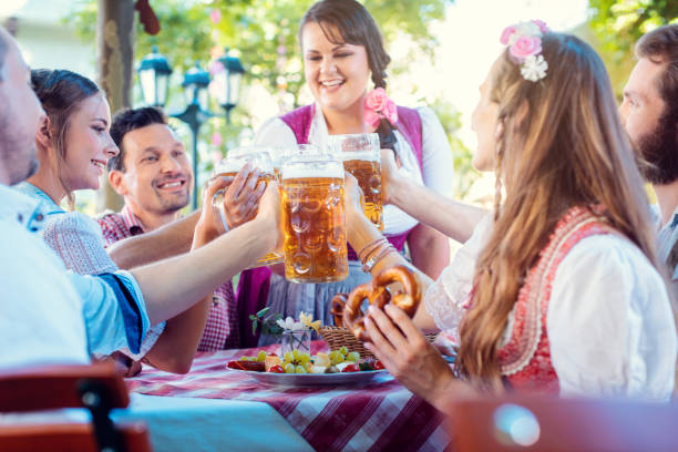 Cheerful friends toasting in Bavarian beer garden Cheerful group of friends toasting in Bavarian beer garden oktoberfest stock pictures, royalty-free photos & images