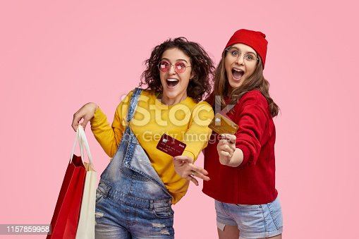 Two satisfied women in colorful outfits holding paper bags and demonstrating credit cards to camera during happy shopping against pink background
