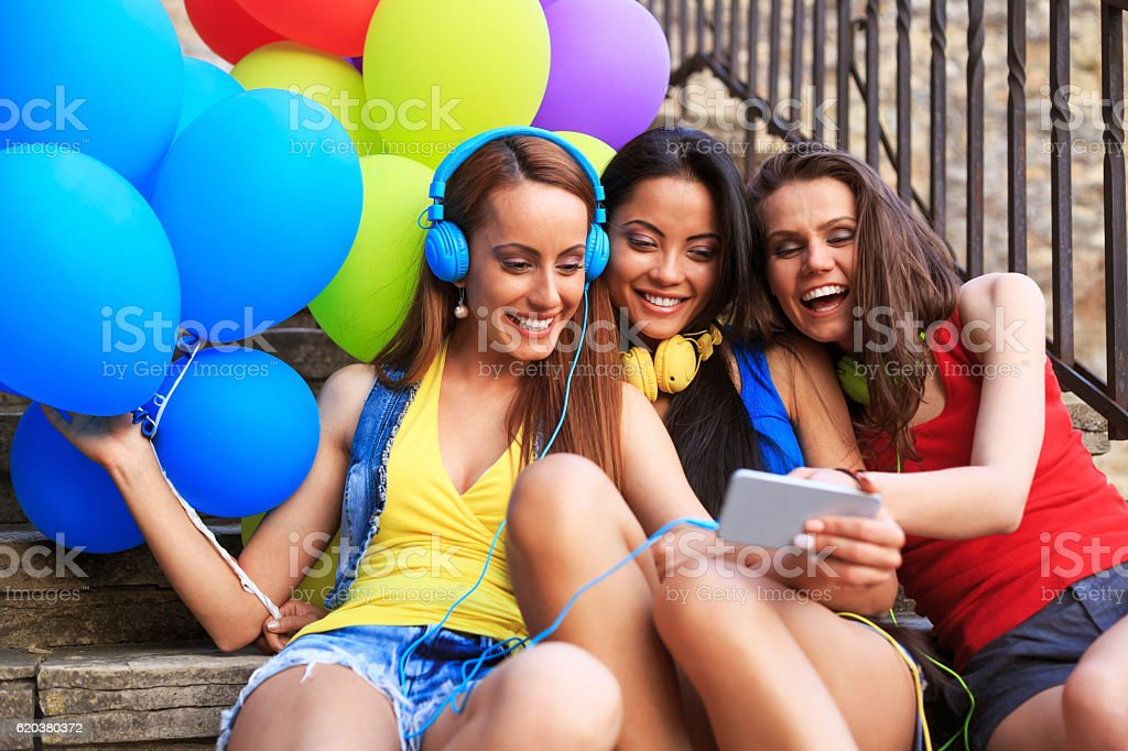 Cheerful friends with headphones sitting on stairs and making selfie zbiór zdjęć royalty-free