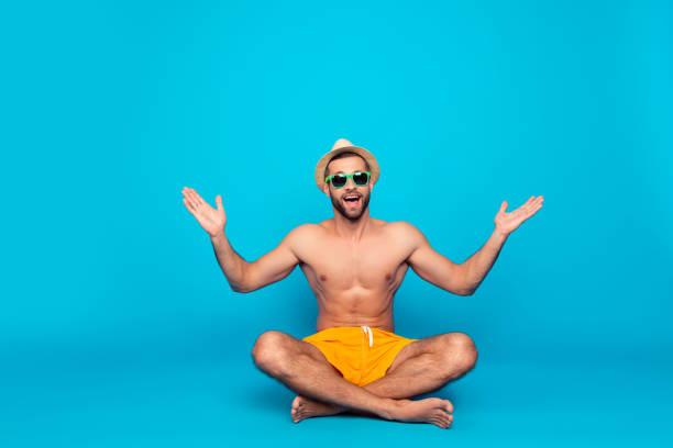 alegre, divertida, atraente, sedutor com torso nu em shorts amarelos sentado com pernas cruzadas sobre fundo azul, desfrutando, admiro o tempo, natureza, férias com as mãos levantadas e abrir a boca - tronco termo anatômico - fotografias e filmes do acervo