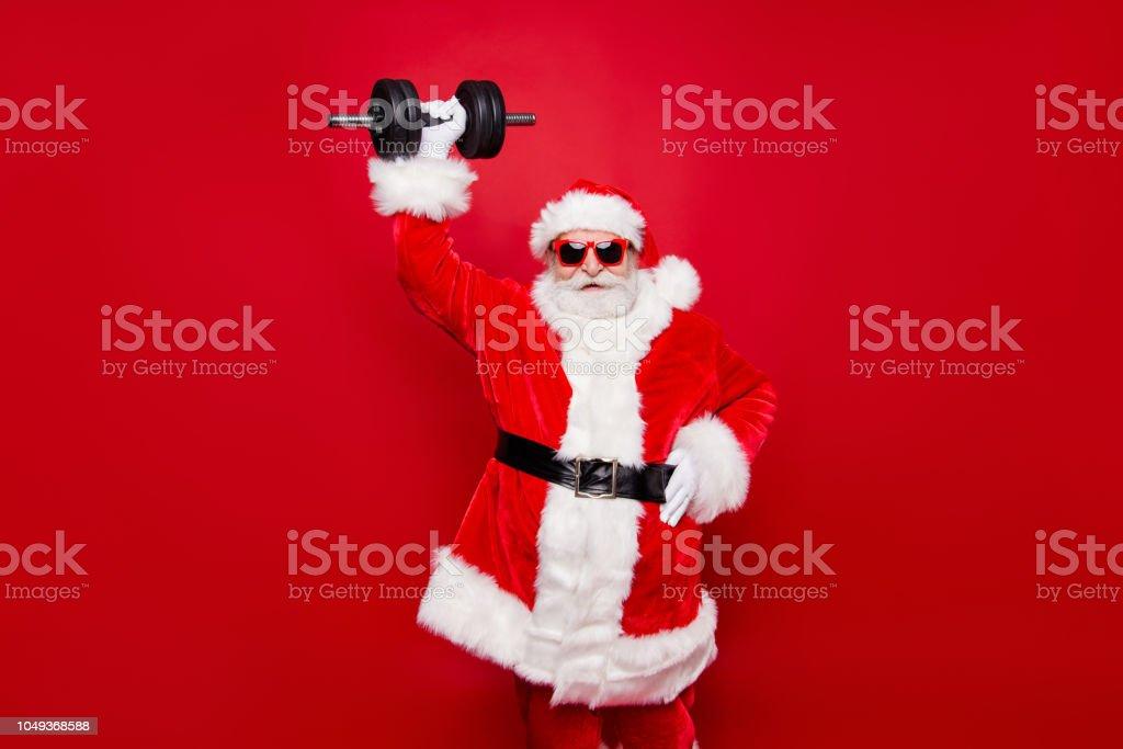 Alegre divertida moda elegante moda fuerte deportivo viril muscular Santa en gafas guantes piel blanco invierno rojo capa cinturón negro levantando una pesa grande esfuerzo aislado sobre fondo rojo foto de stock libre de derechos