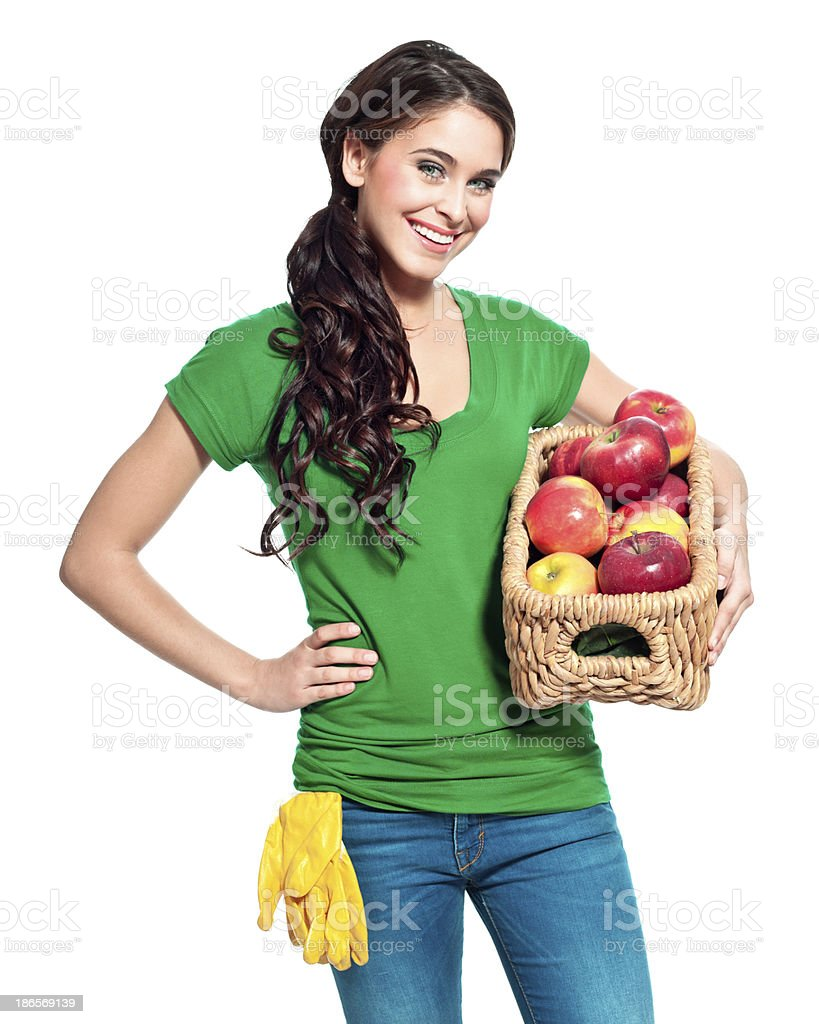 Cheerful gardener with apples Portrait of beautiful gardener holding a basket with apples and smiling at the camera. 20-24 Years Stock Photo