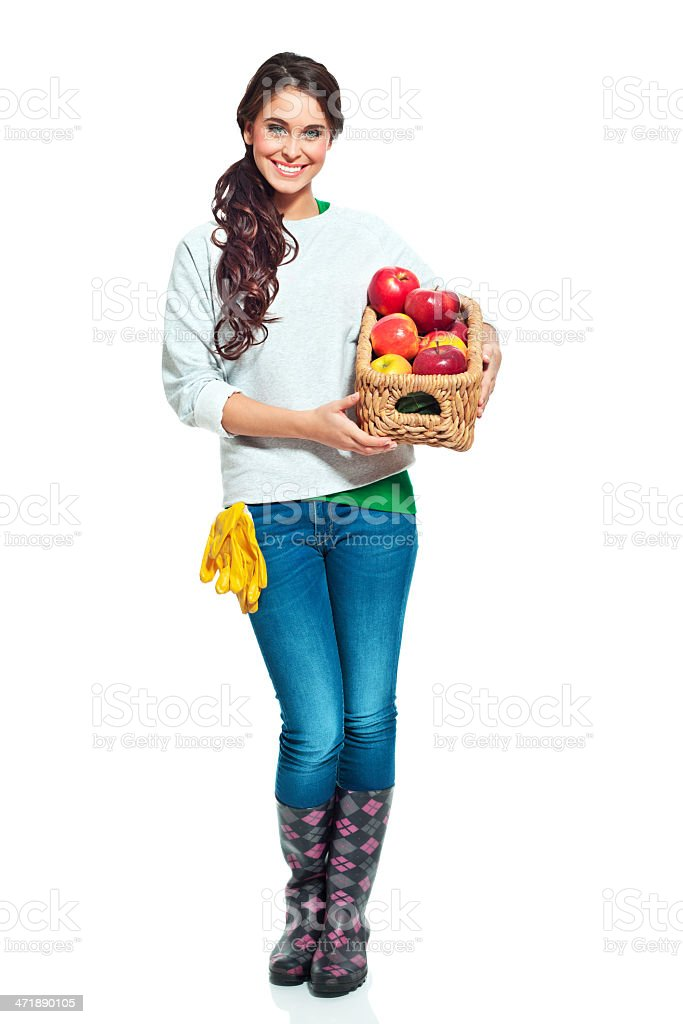 Cheerful gardener with apples Full lenght portrait of beautiful gardener holding a basket with apples and smiling at the camera. 20-24 Years Stock Photo