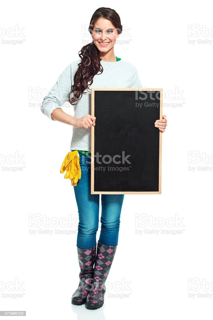 Cheerful gardener with blackboard Full lenght portrait of beautiful gardener holding a blackboard and smiling at the camera. Studio shot, isolated on white. 20-24 Years Stock Photo