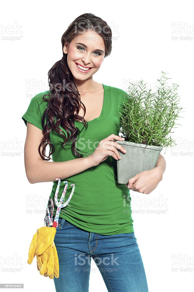 Cheerful gardener with herbs Full lenght portrait of beautiful gardener holding a rosemary in hands and smiling at the camera. 20-24 Years Stock Photo