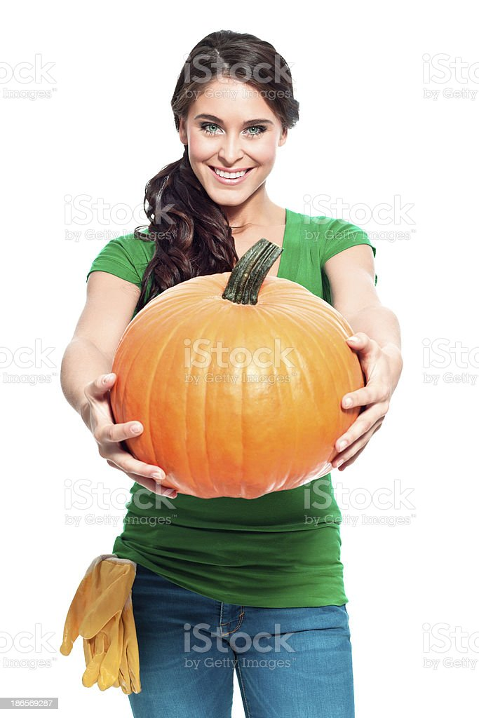 Cheerful gardener with pumpkin Portrait of beautiful gardener holding a perfect pumpkin in front of her and smiling at the camera. 20-24 Years Stock Photo