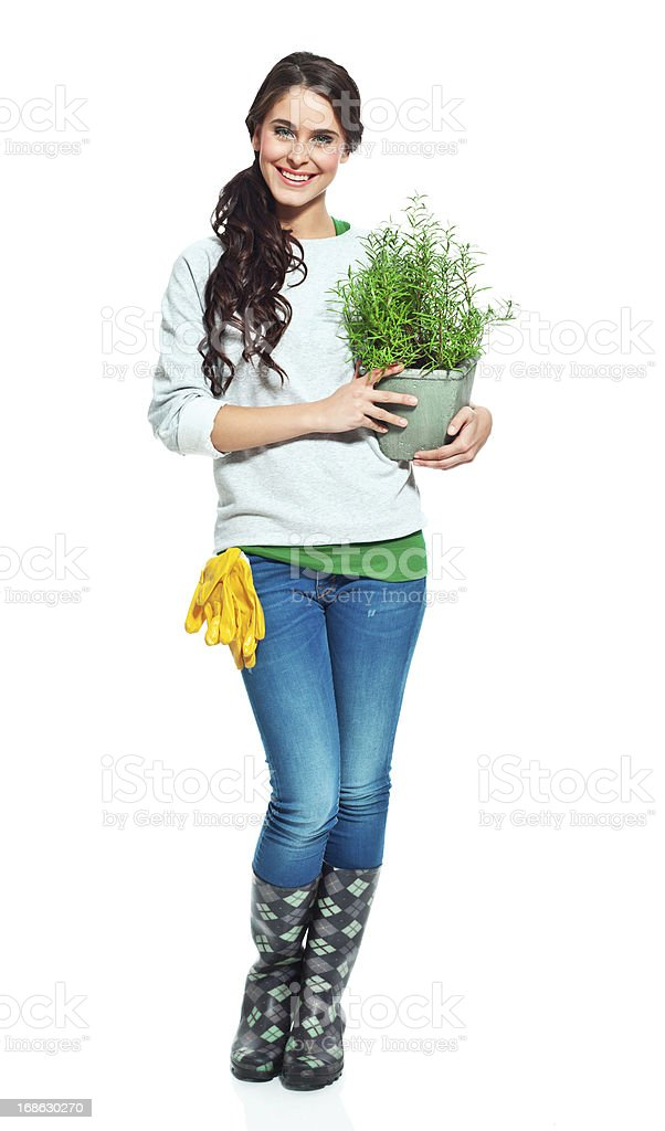 Cheerful gardener with rake Full lenght portrait of beautiful gardener holding a rosemary in hands and smiling at the camera. 20-24 Years Stock Photo