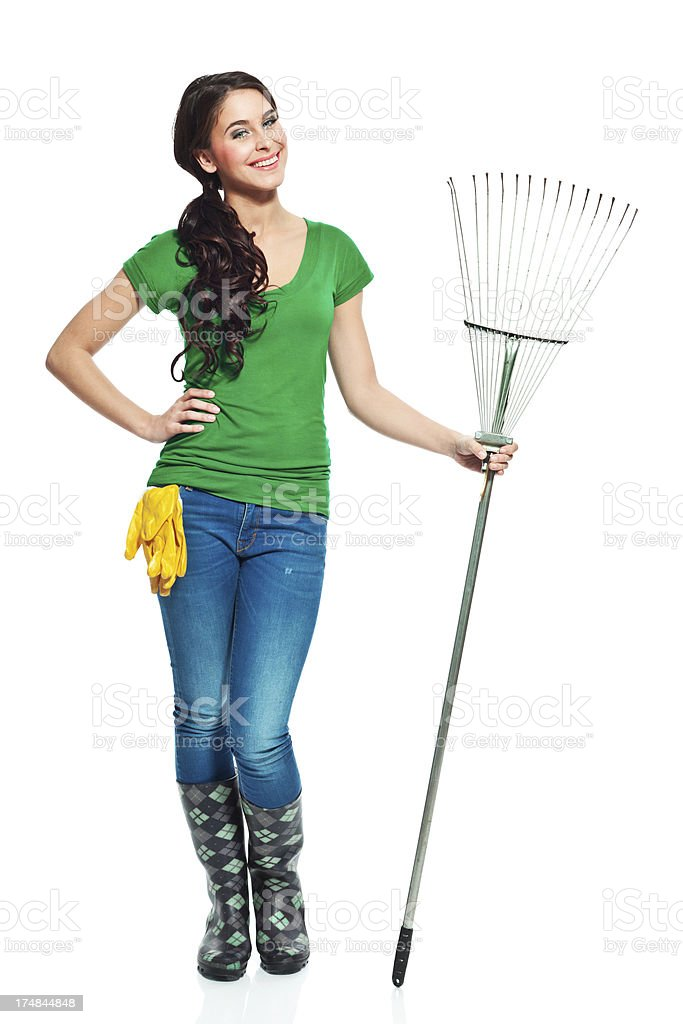 Cheerful gardener with rake Full lenght portrait of beautiful gardener standing with a rake and smiling at the camera. 20-24 Years Stock Photo
