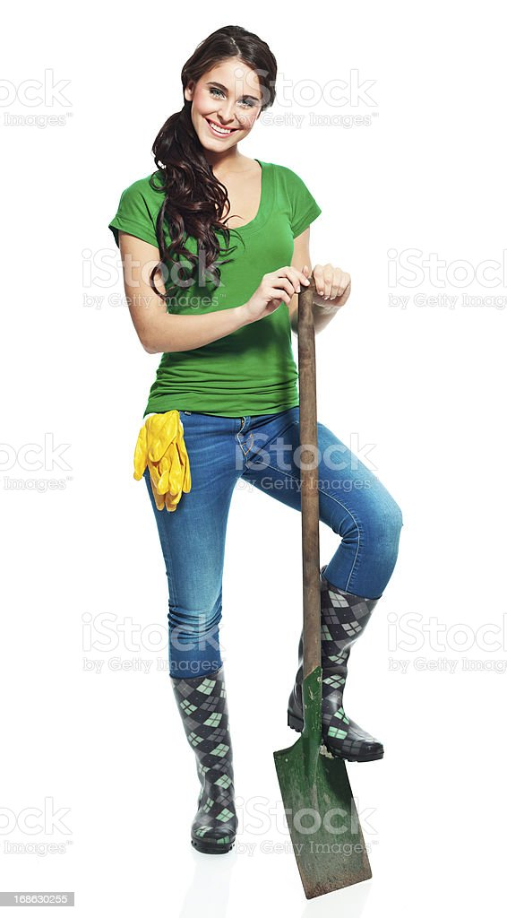 Cheerful gardener with spade Full lenght portrait of beautiful gardener standing with a spade and smiling at the camera. 20-24 Years Stock Photo
