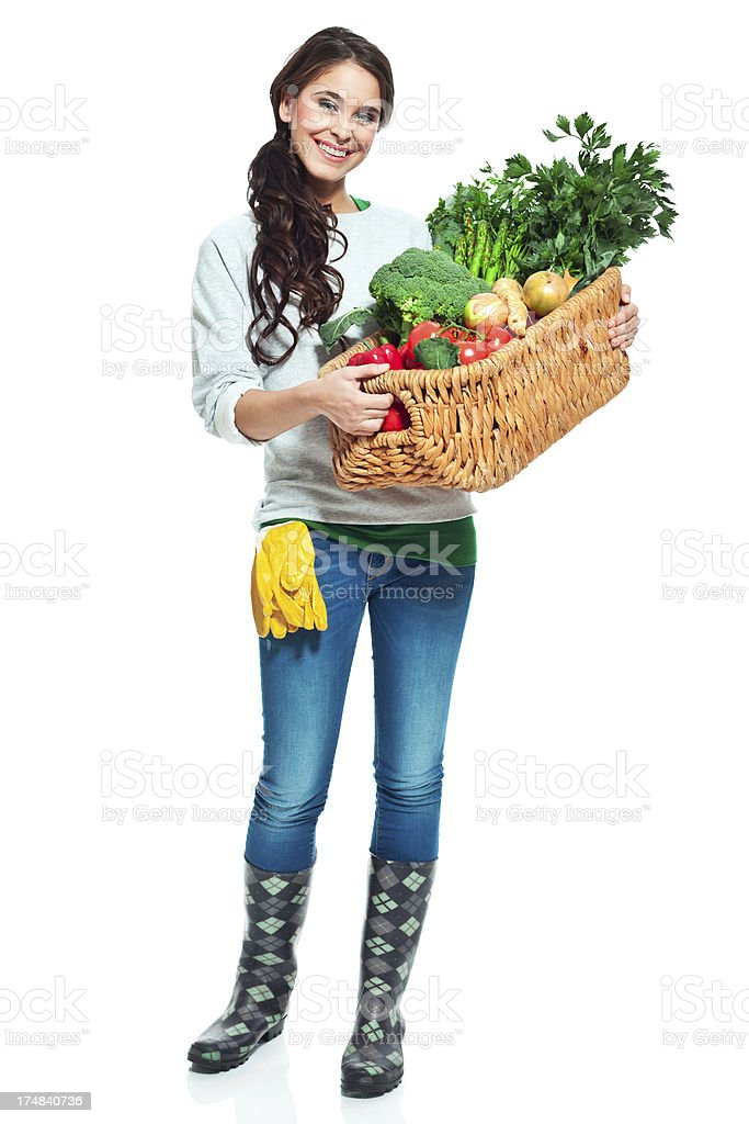 Cheerful gardener with vegetables Full lenght portrait of beautiful gardener holding a baset with home grown vegetables and smiling at the camera. 20-24 Years Stock Photo