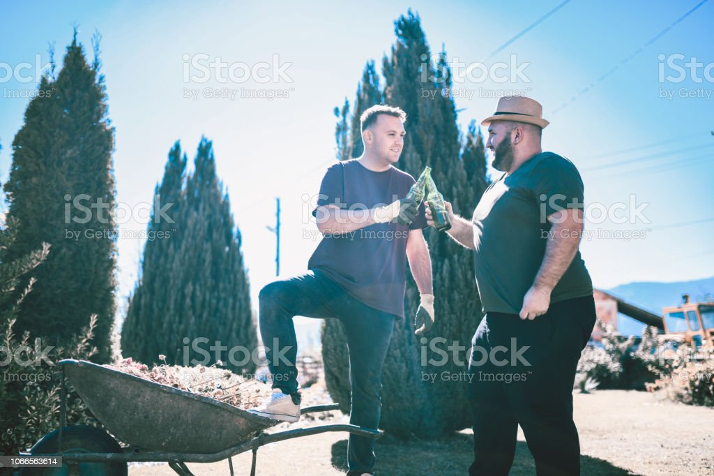 Cheerful Gardeners Making a Toast With Beers stock photo