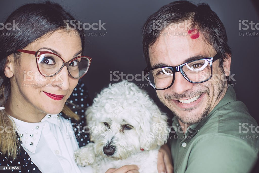 Cheerful geeks embracing a pet stock photo