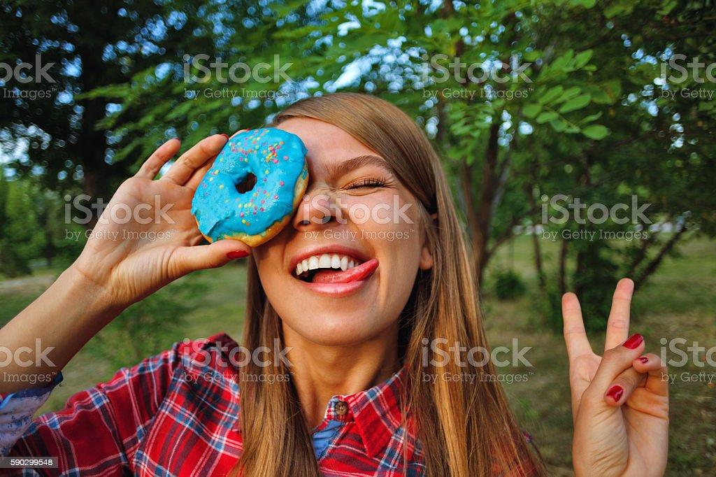 Cheerful girl and a donut royaltyfri bildbanksbilder