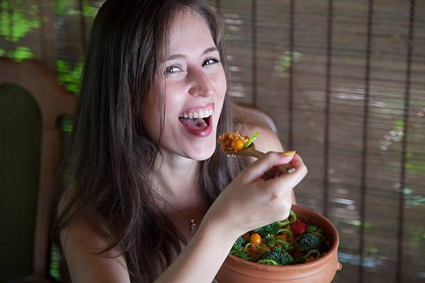 fröhliche frau isst vegane auflauf. - quinoa superfood stock-fotos und bilder
