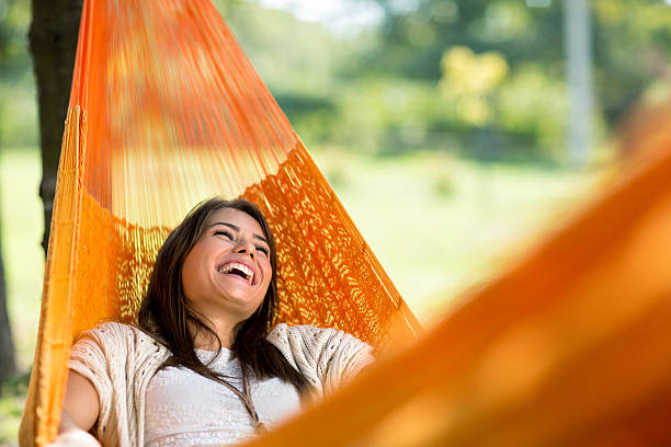 cheerful girl enjoy in hammock - rusten stockfoto's en -beelden