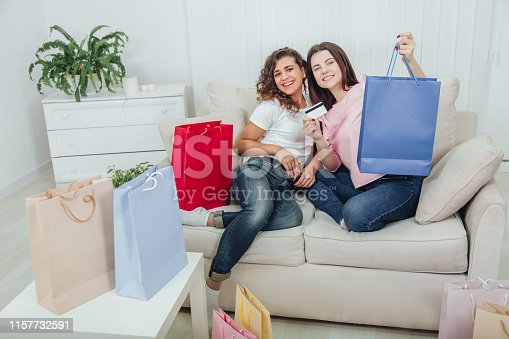 Shopping and friendship concept. Home atmosphere. Full-length shot of two lovely girls.