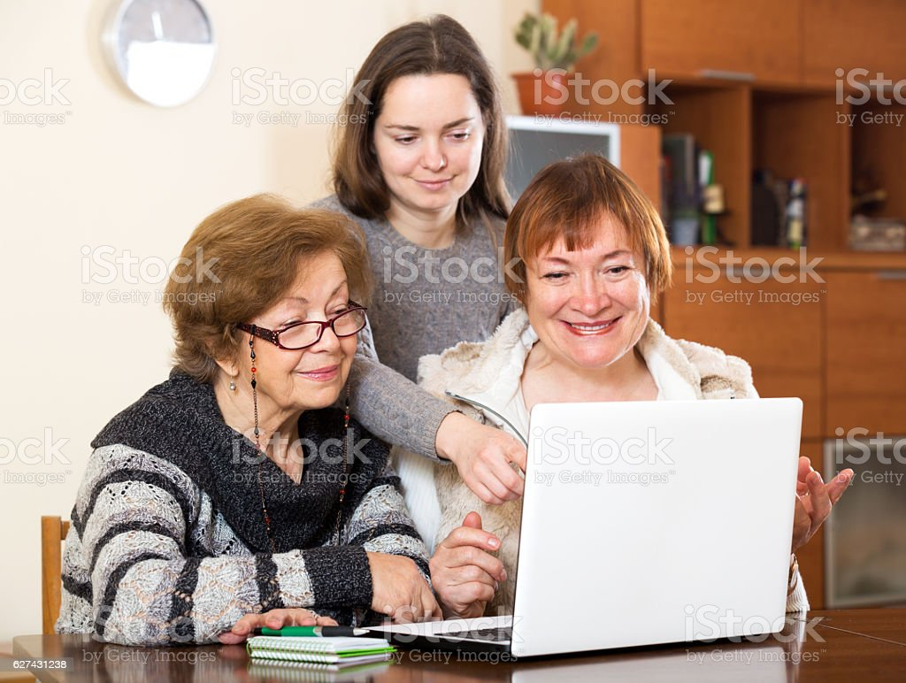 Cheerful girl helping senior women stock photo