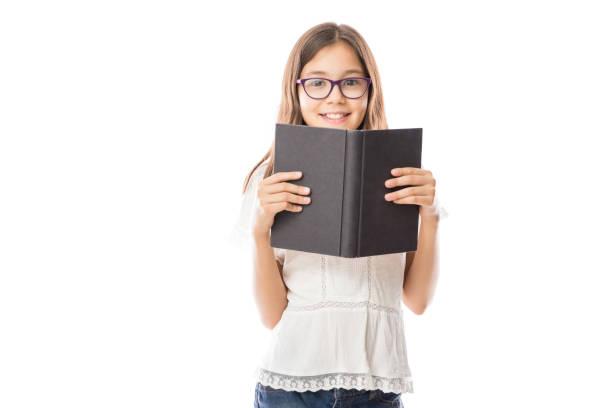 vrolijk meisje houdt een boek camera kijken - a little girl reading a book stockfoto's en -beelden