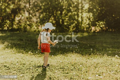 istock Cheerful girl in red shorts and a hat runs around the summer park and playing. 1154745238