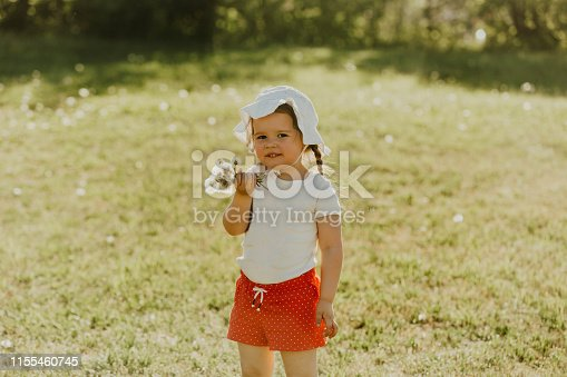istock Cheerful girl in red shorts and a hat runs around the summer park, smiling and playing. 1155460745