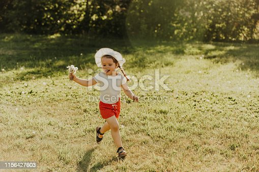 istock Cheerful girl in red shorts and a hat runs around the summer park, smiling and playing. 1156427603