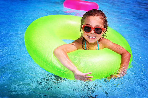 Cheerful girl in swimming pool stock photo