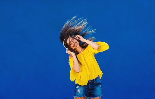 istock Cheerful girl in yellow shirt standing against blue wall with headset on her head. Dancing and smiling. 1032724268