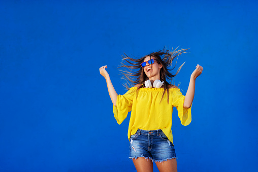 istock Cheerful girl in yellow shirt standing against blue wall with headset around her neck. Dancing and smiling. 1032724364
