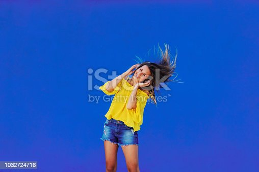 istock Cheerful girl in yellow shirt standing against blue wall with headset on her head. Dancing and smiling. 1032724716