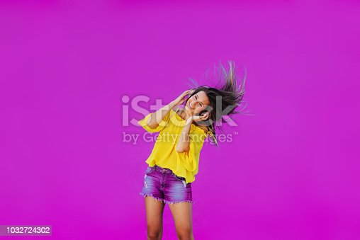 istock Cheerful girl in yellow shirt standing against pink wall with headset on her head. Dancing and smiling. 1032724302