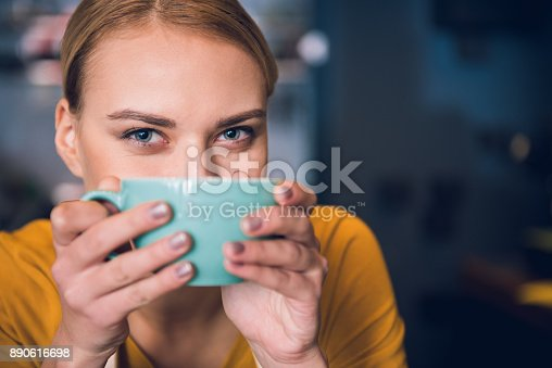 istock Cheerful girl keeping mug near mouth 890616698