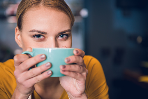 Outgoing young woman closing face by cup of appetizing tea in cafe. Copy space. Pleasure concept