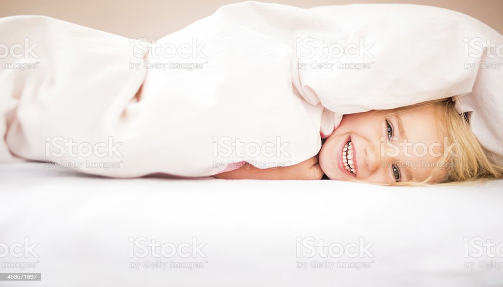 Cheerful girl laughing in bed royalty-free stock photo