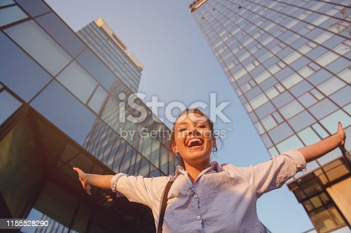 624206636 istock photo Cheerful girl laughs in the middle of a big avenue 1155528290