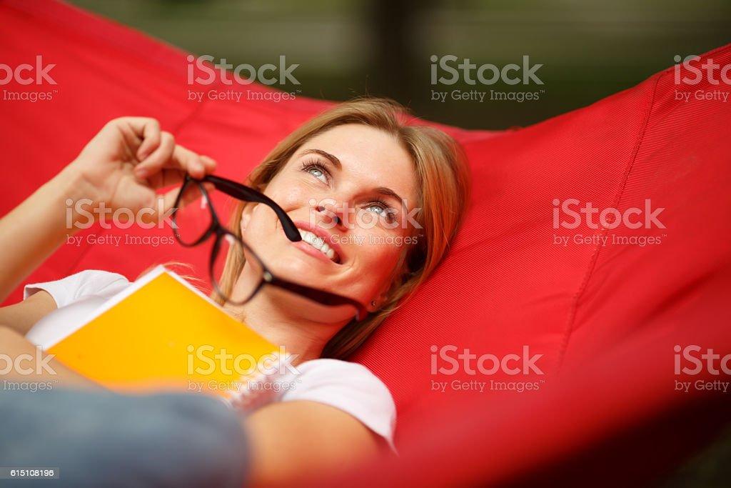 Cheerful girl lies on hammock stock photo