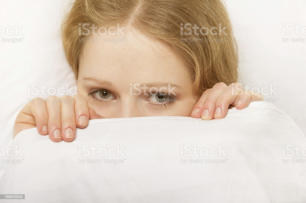 cheerful girl looks out from under the blanket royalty-free stock photo