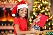 Happy African American girl wearing Santa's hat is making Christmas card and looking at the camera.