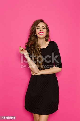 Smiling elegance woman in classic black mini dress. Three quarter length studio shot on pink background.