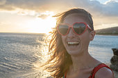 Portrait of young woman wearing heart shape red sunglasses at sunset on beautiful beach - Saint Valentine concept