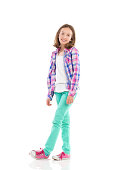Cheerful little girl posing in lumberjack shirt and green trousers. Full length studio shot isolated on white.