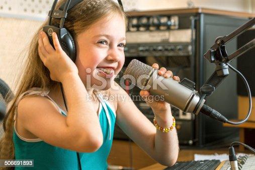 Little girl radio DJ is talking with radio audience in radio studio