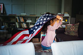Side view of cheerful girl running with American flag. Child is holding national flag in living room. She is enjoying at home.