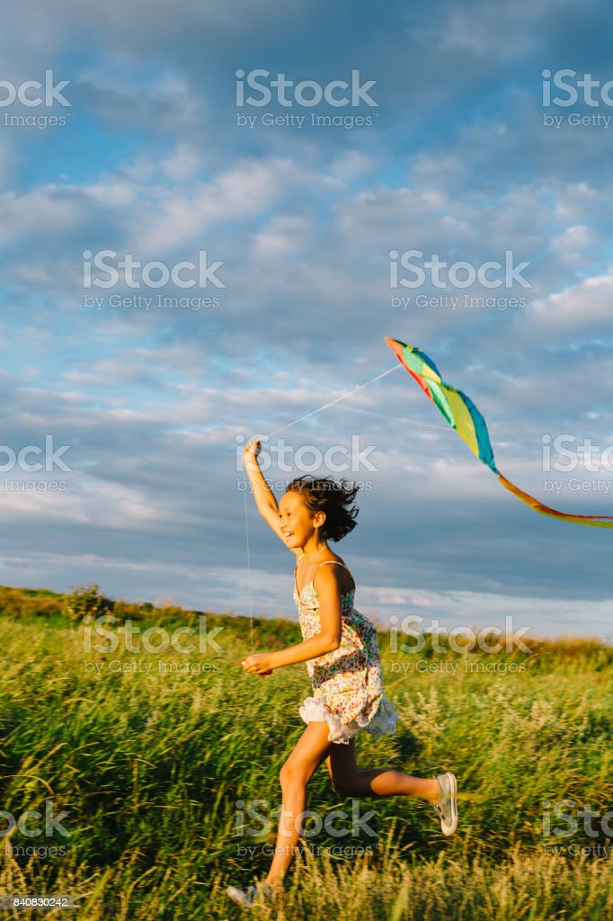 Cheerful girl running with kite stock photo