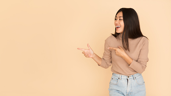 Cheerful Girl Showing Empty Space With Fingers