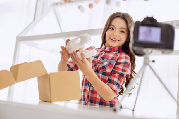 fröhliches mädchen zeigt ihre parzellen inhalte während der aufnahme vlog - kinder verpackung stock-fotos und bilder
