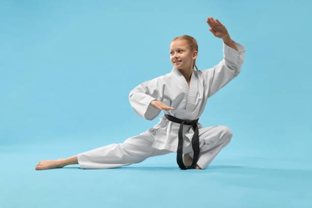 fille gaie s'asseyant sur la ficelle et pratiquant le karaté - arts martiaux photos et images de collection