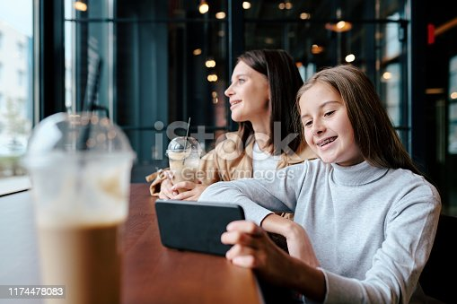 Cheerful girl watching funny video in smartphone while sitting in cafe with her mother on background looking through window