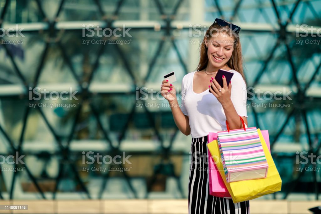 Cheerful girl with a phone, a bank card and shopping at the mall....